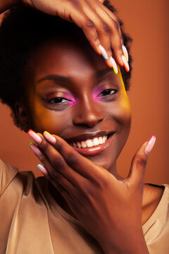 young pretty african girl with bright colorful makeup and manicure posing cheeful on brown background, lifestyle people concept