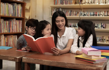 The beautiful lady reading book with three children with happy feeling,blurry light around