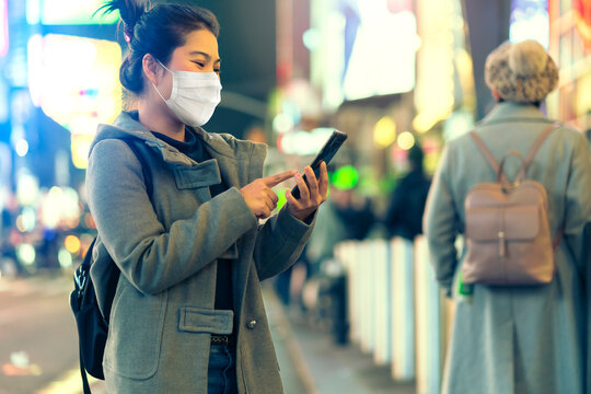 attractive asian female tourist wear surgical mask while travel in center times square downtown new normal travel lifestyle in state