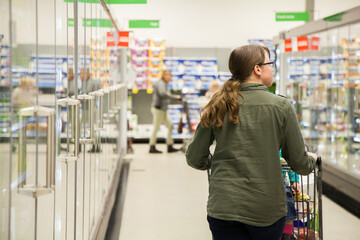 Teen girl pushing shopping trolley down cold aisle in supermarket