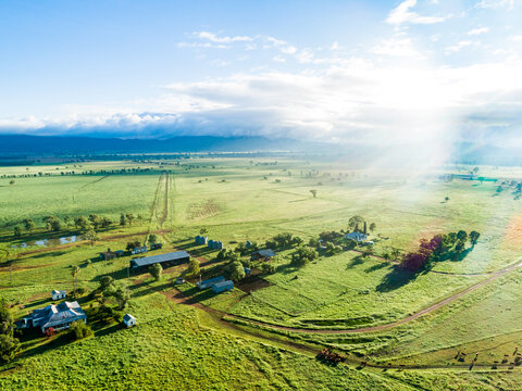 Morning sunlight bursting over small country farmstead and green paddocks