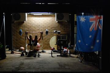 A young man doing weights at night near an Australian flag