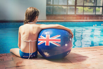 girl on the side of a swimming pool with an Australian flag ball