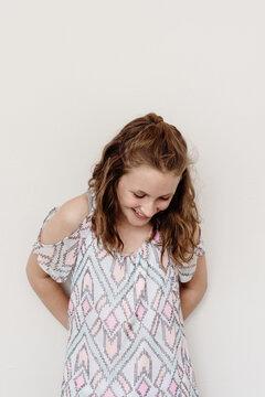 Teen girl against a blank wall