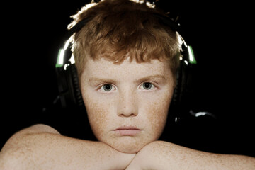 freckled teenage boy looking at cameras with headphones on