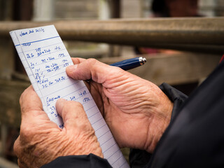 Stock agent and his notes for the day at the cattle sale