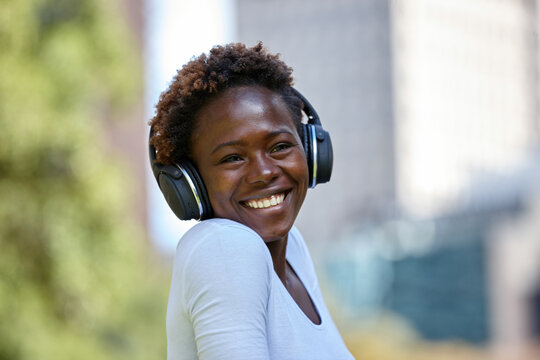 Happy young African woman listening to music wearing wireless headphones in city