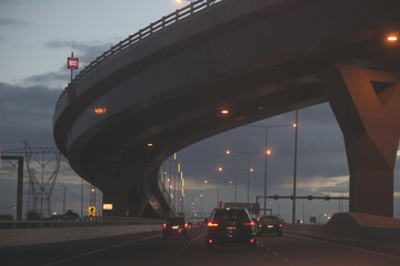 Cars passing under a bridge on Melbourne City roads in the evening Fotomurales