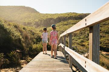 Two girls walking along a boardwalk