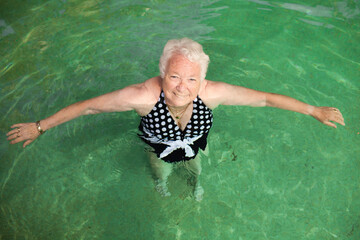 Elderly lady relaxing in a swimming pool