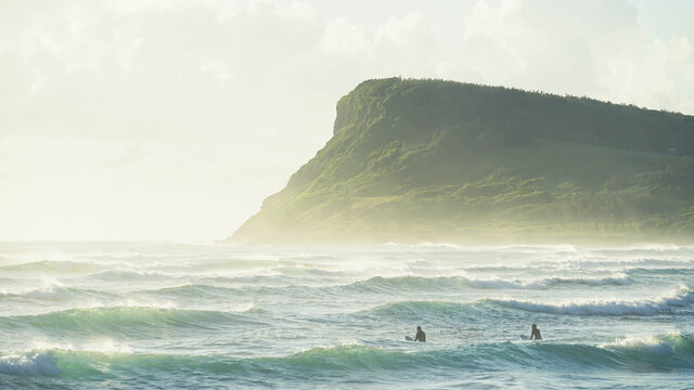 Men surfing in sea with Lennox Headland in background