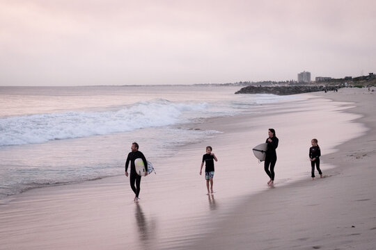 Family of two adults and two children walking along the beach carrying surfboards dressed in wetsuit
