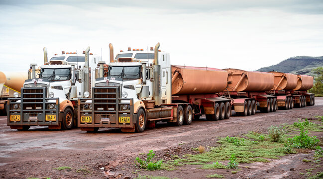 Two big road train trucks side by side on outback road