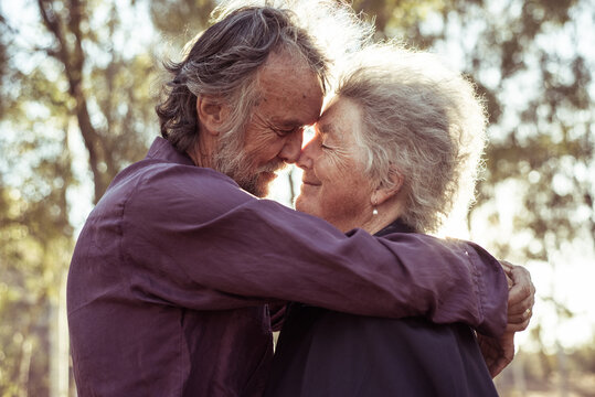 Smiling senior couple with eyes closed embracing each other outdoors