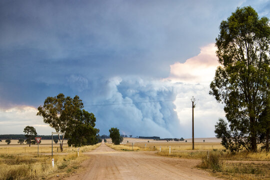Country road with bushfire smoke in the distance