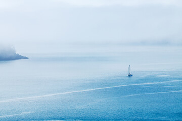 yacht sailing into sea fog
