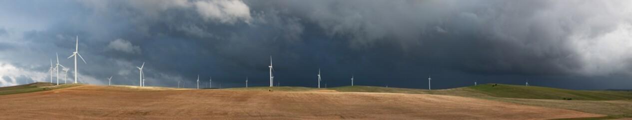 black storm clouds behind wind turbines