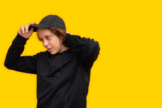teen boy dressed in black with cap on yellow background