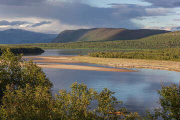 Scenic view of the mountain river flowing into Laksefjord of the Barents sea in Finnmark, Norway