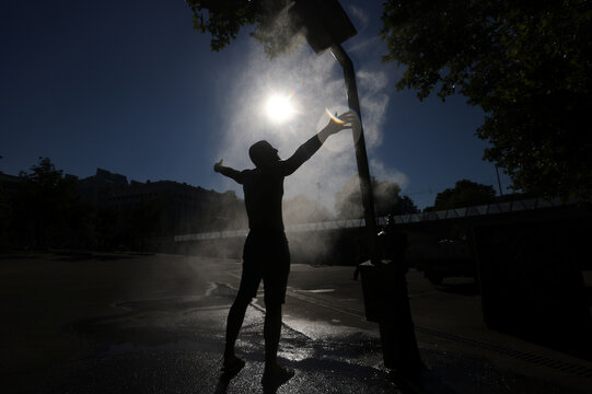 A man cools off under a water sprinkler during a hot summer day in Vienna