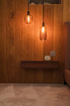 Modern pendant lights hanging over wooden shelf with alarm clock