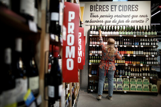 An employee prepares bottles of beer and cider as she restocks a sales display inside a Naturalia organic foods grocery store operated by Casino Group, in Bretigny-sur-Orge