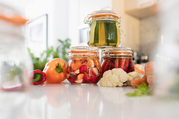 Pickled vegetables in jars on kitchen counter