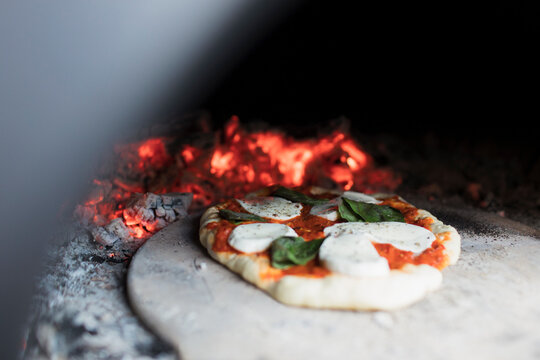 Close up homemade pizza on peel in pizza oven