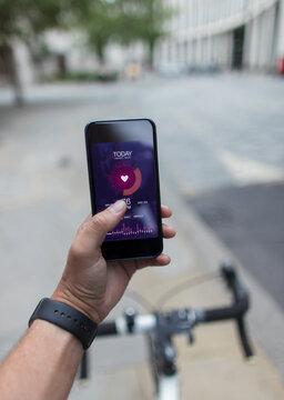 POV Man on bicycle using smart phone health app