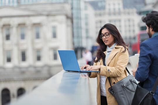 Business people using laptop on city bridge