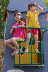 Poster de jardin Doux monstres Two sistres sitting on the balcony of a toy house. Little girl looks away. Happy summer time.
