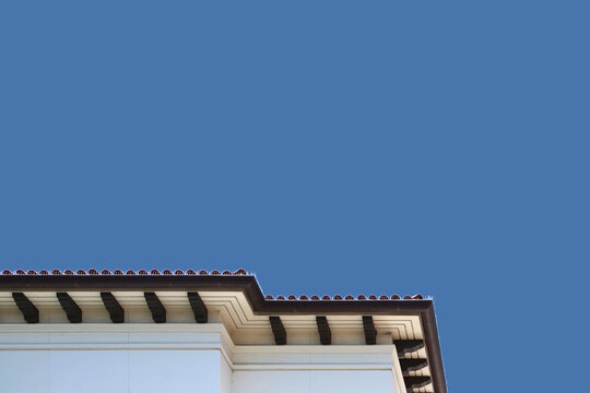Low angle view of the edge of a large building in the southern California modern Spanish heritage style under blue sky