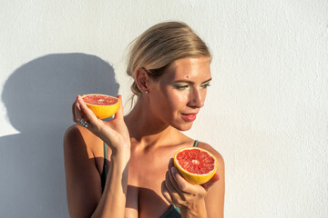 Beautiful young woman in swimsuit with a grapefruit. Fashion summer concept.