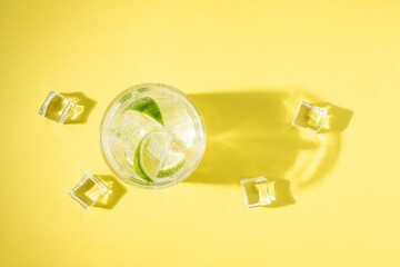 Refreshing lemonade in a glass on a bright background. Summer drink concept.