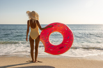 Happy woman with inflatable donut on a tropical beach. Summer vacation concept.