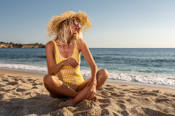 Young woman sitting on a tropical beach. Summer vacation concept.