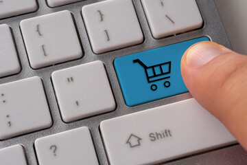 Male hand pressing keyboard button with shopping cart. Shopping online concept.