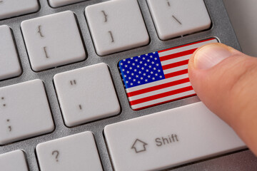 Male hand pressing keyboard button with flag of USA on it. Online international business concept.