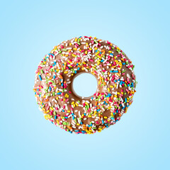 Donut with sweet color decoration on bright background. Minimal food concept.