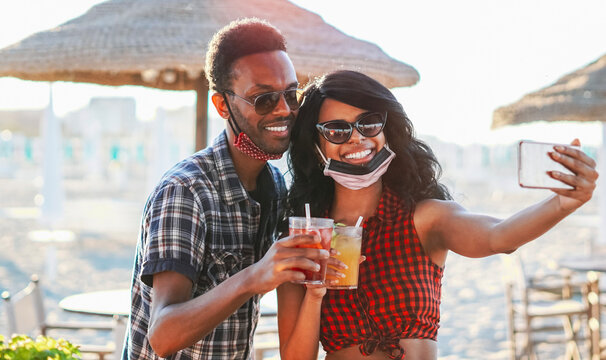 African american couple taking selfie in beach party - Young friends with face mask drinking cocktail in holiday - Coronavirus summer 2020