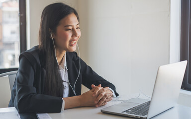 Working from home using internet communication concept. Asian young woman wear earphones talking  in video conference with business partners and worker team via online internet at her home.