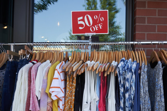 Discounted fashion dresses, sweaters, and jeans hanged on a clothes rack outside a retail store. Sidewalk sale.
