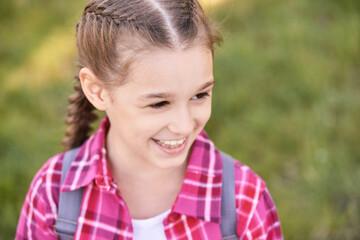 Young schoolgirl with backpack. Laugh. Lifestyle elementary school. Funny girl. Outdoor autumn park. Children learn smart. Street student. Happy preschool kid. Back to school