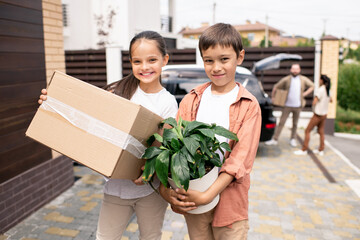Portrait of positive cute kids holding potted plant and cardboard box in front yard of new house