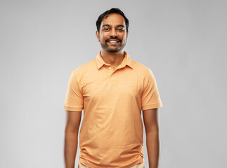 people and furniture concept - portrait of happy smiling young indian man over grey background