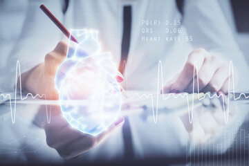 Heart hologram over woman's hands writing background. Concept of Medical education study. Double exposure