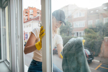 Young woman cleaning window from outside