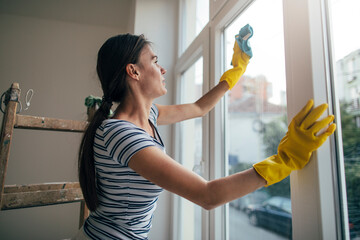 Woman in yellow gloves cleaning window with rag
