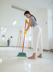 Woman cleaning floor with brush