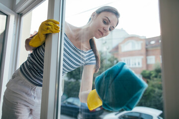 Young woman in gloves cleaning window with rag